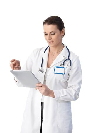 Doctor checking medical data on tablet pc, smiling, cutout on white. photo