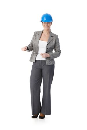 Portrait of smiling female engineer wearing protective hat, standing holding clipboard, looking at camera, cutout on white. Stock Photo - 9868515