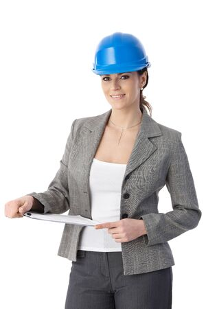 executive helmet: Engineer woman in hardhat holding clipboard, smiling at camera. Stock Photo