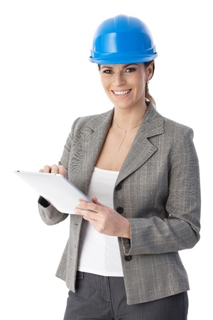 Laughing architect woman standing, wearing hardhat, with touchscreen computer handheld, looking at camera. photo