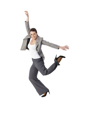 Jumping elegant woman smiling, posing in studio, smiling, arms wide open, leg in air, full length, cutout on white. photo
