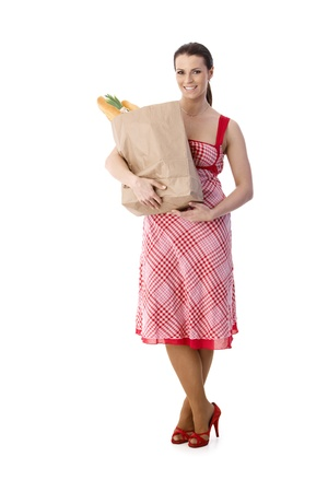Housewife holding food shopping bag, standing in pretty dress, wearing high heels, full length portrait, cutout on white. photo