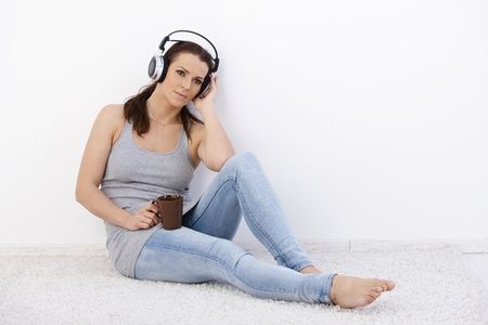 Mid-adult woman enjoying music via headphones, holding coffee mug, sitting on floor, daydreaming. photo