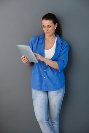 one mid adult woman only: Casual mid-adult woman standing at wall, using touchscreen computer, smiling. Stock Photo