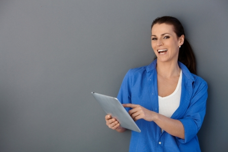 Laughing woman using touchscreen computer, pointing at screen, looking at camera. photo