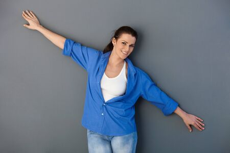 outspreading: Portrait of attractive mid-adult woman posing at grey wall with arms wide open, smiling at camera.