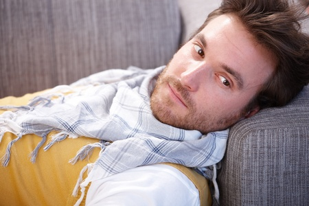 bristly: Handsome young man laying on sofa at home, daydreaming, looking away.