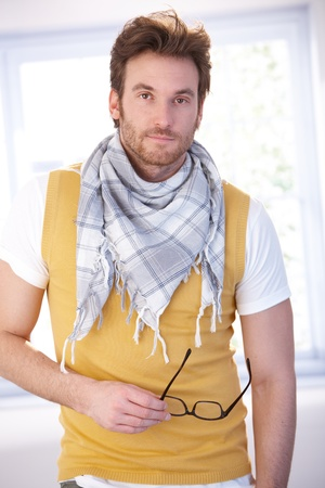 offish: Goodlooking young man standing front of window at home, wearing vest and scarf.