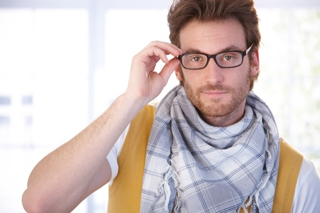 offish: Young man standing front of window in living room, wearing glasses, looking at camera. Stock Photo