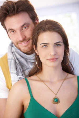 Portrait of nice young couple, embracing, smiling at camera. photo