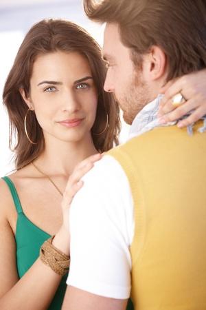 Beautiful young woman hugging man, looking at camera. Stock Photo