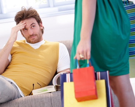 Young man looking troubled when shopaholic woman arriving home with shopping bags. Stock Photo - 10372957