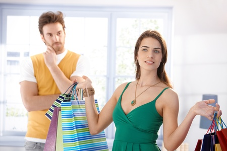 Shopaholic young woman standing in living room, holding shopping bags. Stock Photo - 10372970