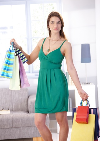 Attractive young woman standing in living room, holding shopping bags, smiling. photo