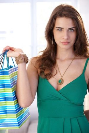 offish: Attractive young woman holding shopping bags, looking at camera.