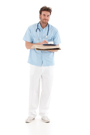 image consultant: Goodlooking doctor writing notes, holding papers, standing, smiling. Stock Photo