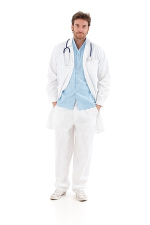 image consultant: Confident young doctor standing with hands in pocket, looking at camera.