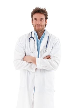 male doctor: Bel giovane medico armi in piedi incrociato, sorridendo a fotocamera. Archivio Fotografico