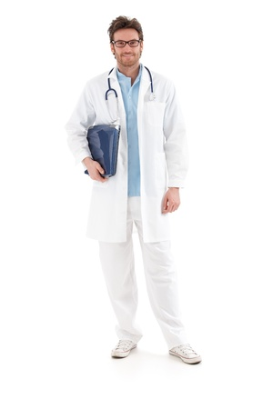 full size: Young doctor smiling with laptop in hand, looking at camera.  .