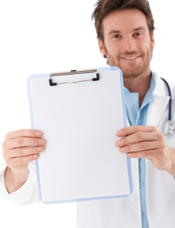 image consultant: Handsome young doctor holding blank sheet in hands, smiling at camera. Stock Photo