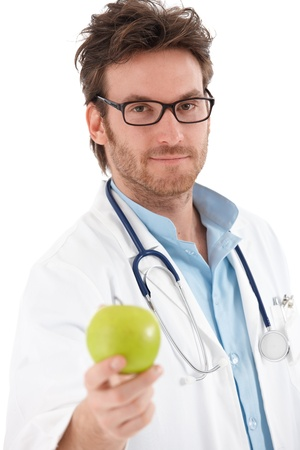 young unshaven: Handsome young doctor holding green apple, looking at camera.