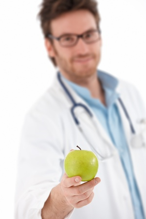 Young doctor offering green apple, smiling. photo