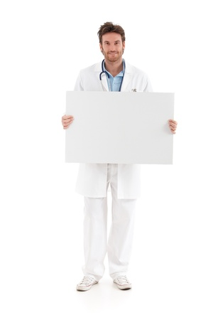 Casual young doctor holding big blank sheet, smiling at camera. photo