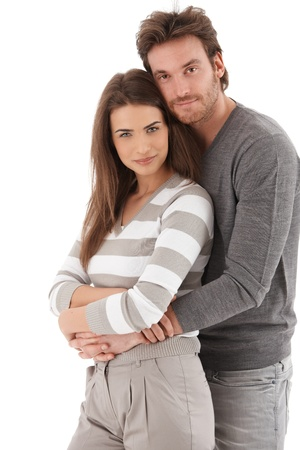 happy couple white background: Portrait of attractive young loving couple smiling at camera, embracing.