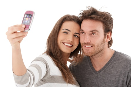 Beautiful loving couple photographing themselves by mobile phone, smiling. photo