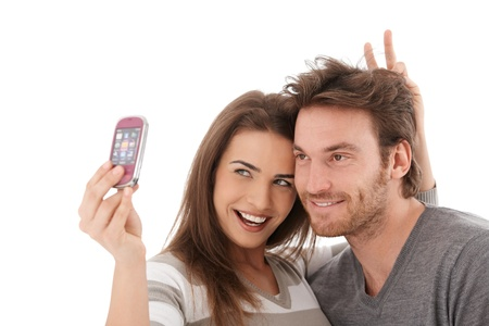 Happy young couple taking a photo of themselves, smiling. photo