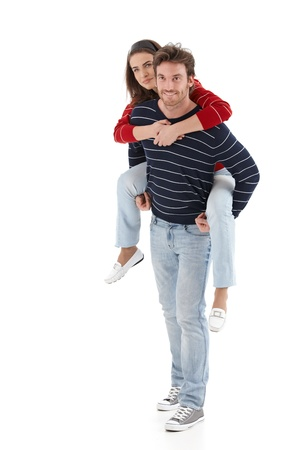 Loving young man carrying woman pickaback, smiling. photo
