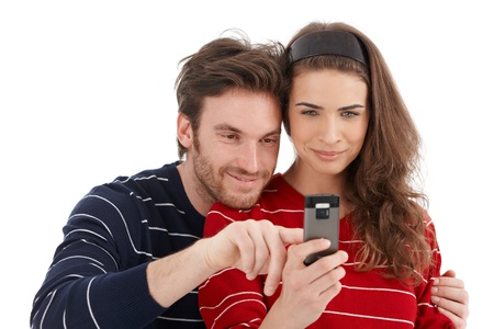 Happy loving couple using mobile phone, smiling. Stock Photo