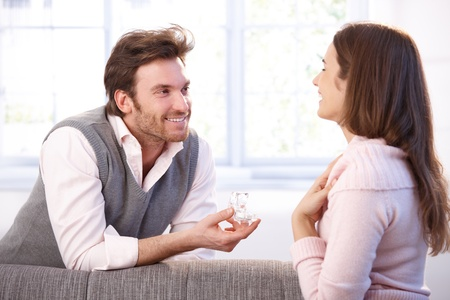 proposing: Happy young couple having engagement, smiling. Stock Photo