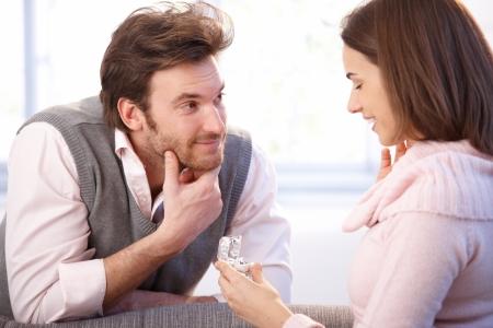 Uomo bello che propone alla donna, dando l'anello di fidanzamento, sorridente. Archivio Fotografico