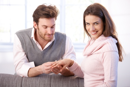 Attractive young couple having engagement, man pulling engagement ring on womans finger, smiling. photo