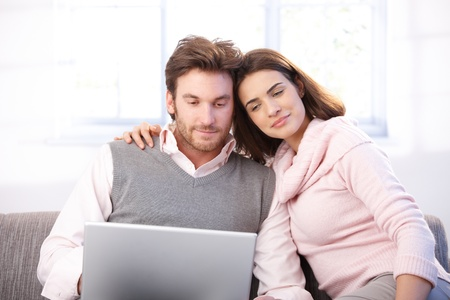 indoor photo: Attractive young couple sitting on sofa at home, embracing, using laptop, smiling.