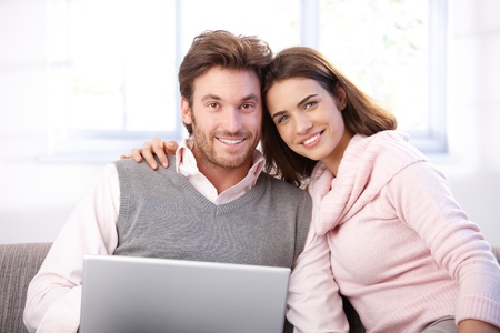 Happy young couple sitting on sofa at home, browxing internet, smiling at camera. photo
