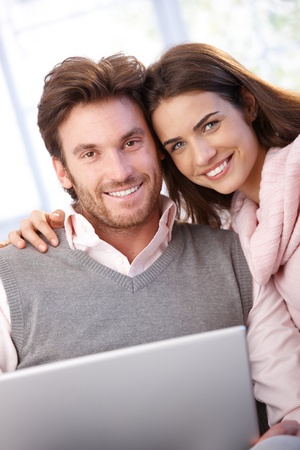 Beautiful young couple using laptop at home, smiling at camera. photo