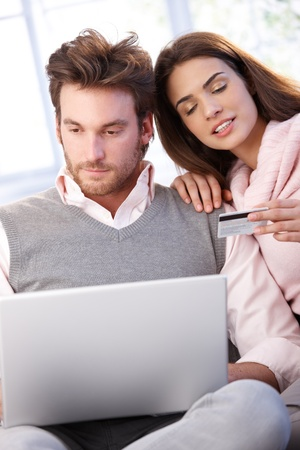 Young couple shopping on internet, having laptop, using credit card. photo