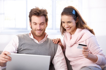 Happy young couple shopping online, using laptop and credit card, smiling. photo