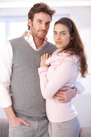 amigos abrazandose: Atractivo joven pareja abraz�ndose, mirando a la c�mara.