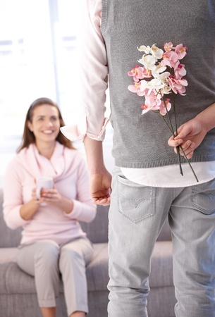 getting together: Young man bringing flowers to woman, woman sitting on sofa, smiling. Stock Photo