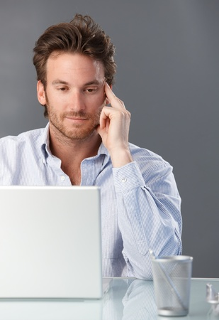 Casual businessman working with laptop computer at office desk, thinking. photo