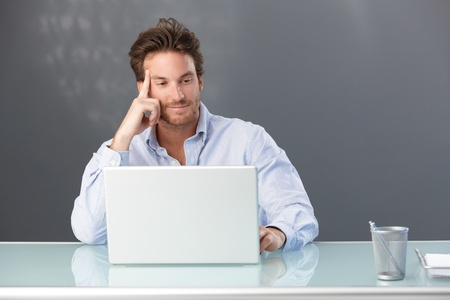 Smiling handsome male office worker sitting at desk looking at laptop computer screen. Stock Photo - 10373381