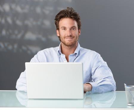 using the computer: Casual empresario sentado en la Oficina con equipo portátil, sonriendo a la cámara.