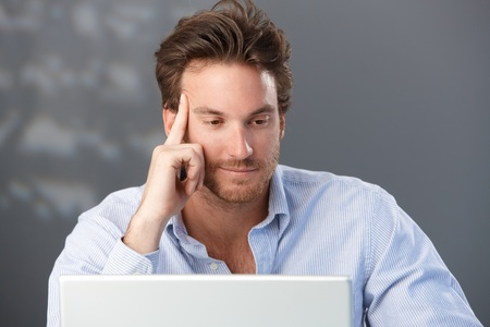 looking at computer screen: Portrait of handsome businessman thinking, looking at laptop computer screen. Stock Photo