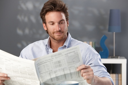 1 man only: Handsome man sitting in living room, reading newspaper, smiling. Stock Photo