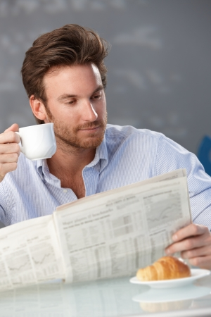 Portrait of goodlooking man drinking coffee and reading morning papers at home.
