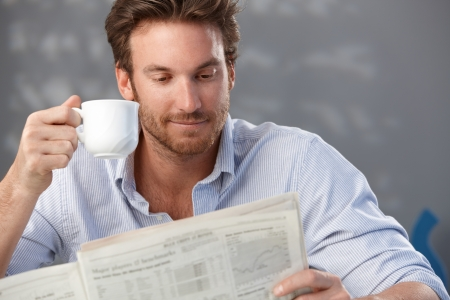 reading room: Morning portrait of handsome guy reading newspaper and holding coffee cup. Stock Photo