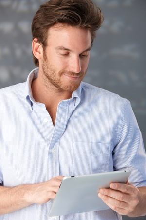 Handsome guy using touchscreen computer, smiling.